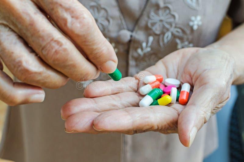 Pillen in der Hand, ältere Frau, die Pille in ihrer Hand hält lizenzfreie stockbilder