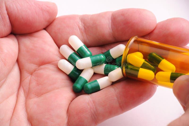 Pillen in der Hand des Mannes lizenzfreie stockbilder