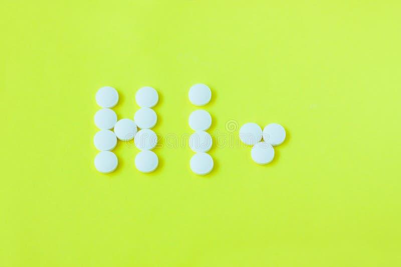Pillen in een vorm van een woord hallo op een gele achtergrond Vlak leg, hoogste mening, minimalistic stijl stock afbeelding