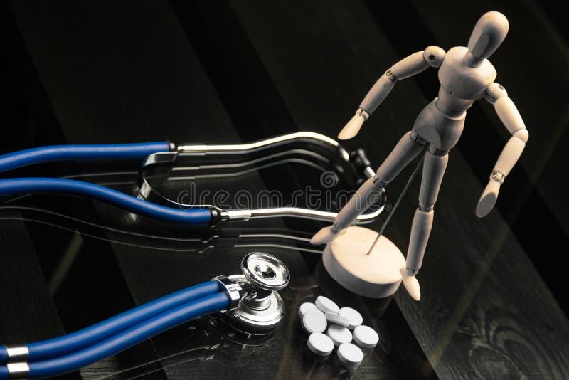 Pillen, ein Stethoskop und eine gefälschte Person auf einem schwarzen Hintergrund stockbild
