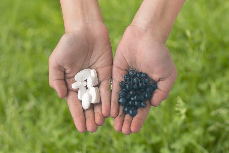 Pillen en bessen in de handen stock fotografie
