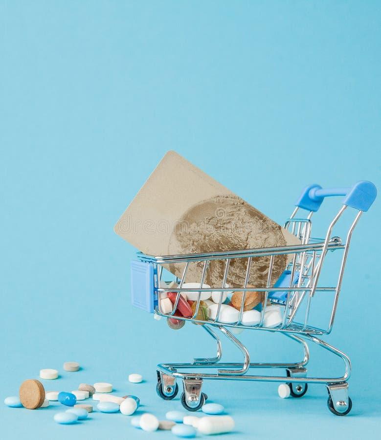 Pillen en creditcard in het winkelen karretje op blauwe achtergrond Creatief idee voor gezondheidszorgkosten, drogisterij, ziekte royalty-vrije stock foto's