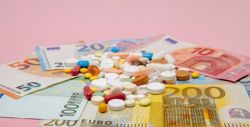 Pillen en euro op een roze achtergrond met exemplaarruimte Zachte nadruk Concept geneeskunde, geld en gezondheid stock afbeelding