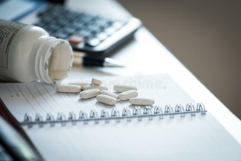 Pillen en fles op notitieboekje in bureau stock afbeeldingen