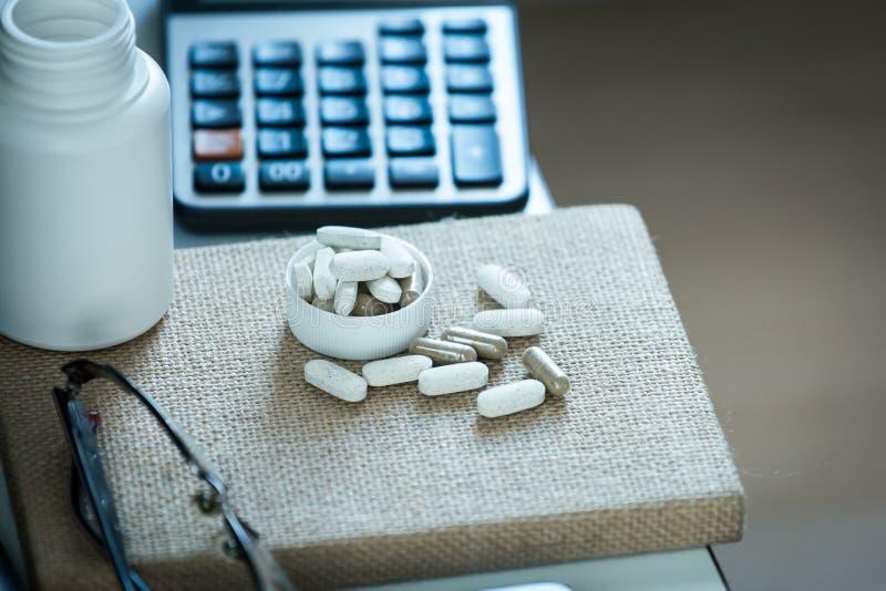 Pillen en fles op notitieboekje in bureau stock foto