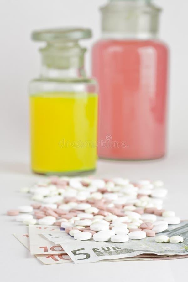 Pillen en geld stock afbeeldingen