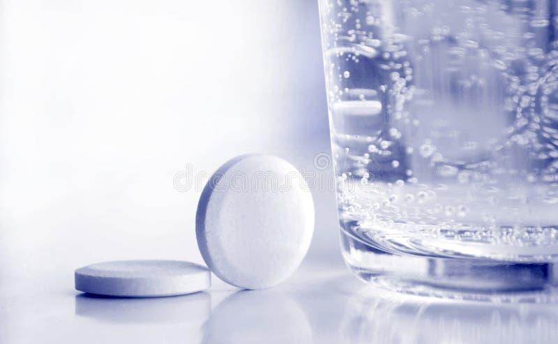 Pillen en glas water stock fotografie