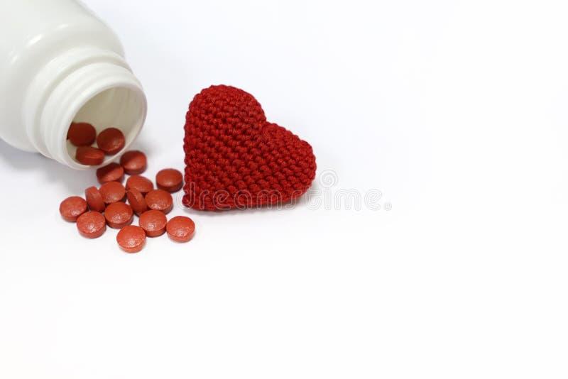 Pillen en rood gebreid die hart op wit worden geïsoleerd royalty-vrije stock foto