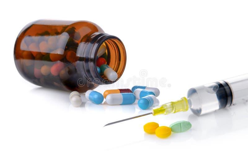 Pillen en spuit met vloeistof op witte achtergrond stock fotografie