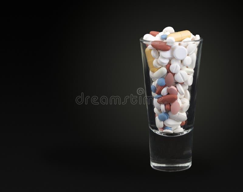 Pillen im Schnapsglas lizenzfreies stockfoto