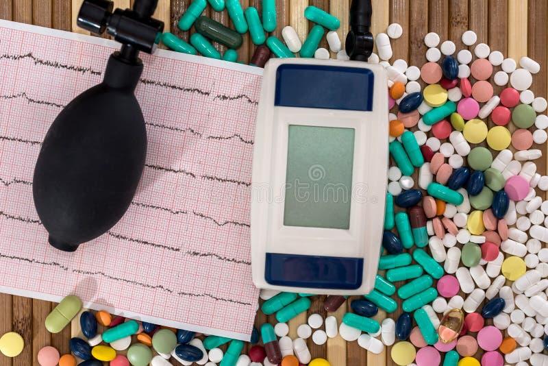 Pillen met cardiogram en tonometer op houten lijst stock afbeeldingen