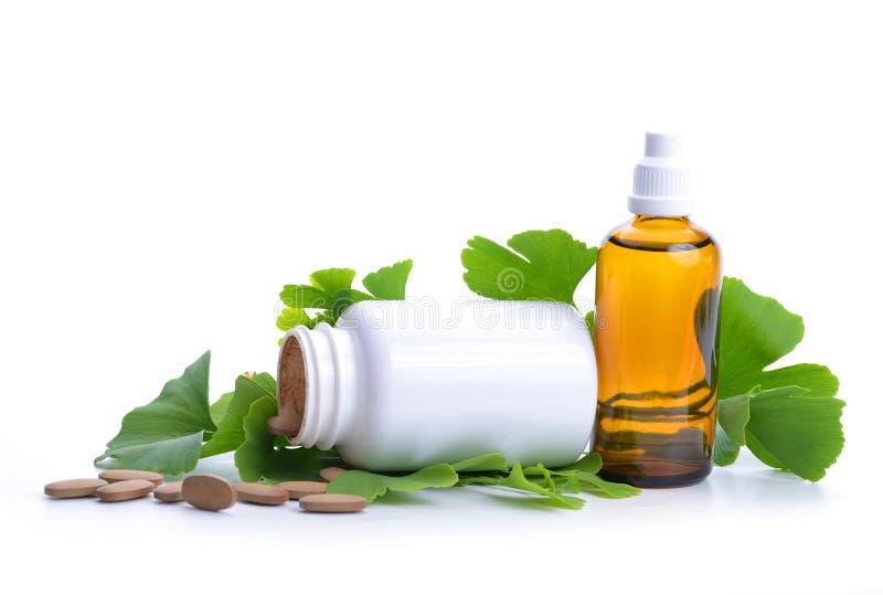 Pillen met uittreksel van ginkgo in fles en groene bladeren royalty-vrije stock foto