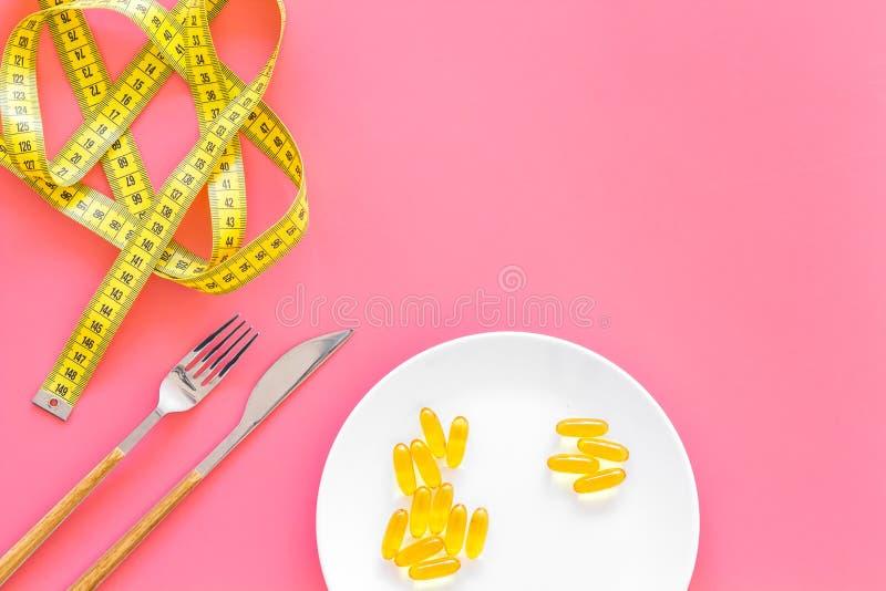 Pillen oder diätetische Ergänzung für Gewichtsverlust Behandlung von Korpulenz Behandlung der Magersucht Goldpillen auf Platte na lizenzfreie stockbilder
