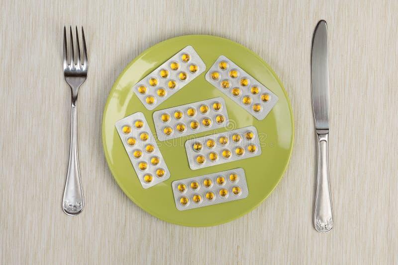 Pillen op blaar, vork en mes stock afbeeldingen