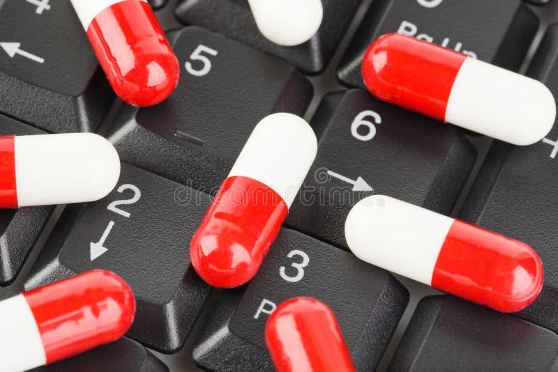 Pillen op computertoetsenbord royalty-vrije stock afbeelding