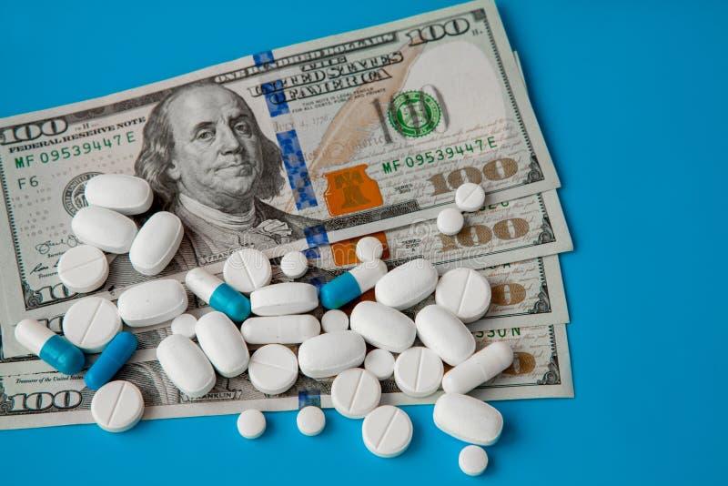 Pillen op dollargeld op blauwe achtergrond Geneeskundeuitgaven Hoge kosten van medicijnconcept Sluit omhoog stock foto