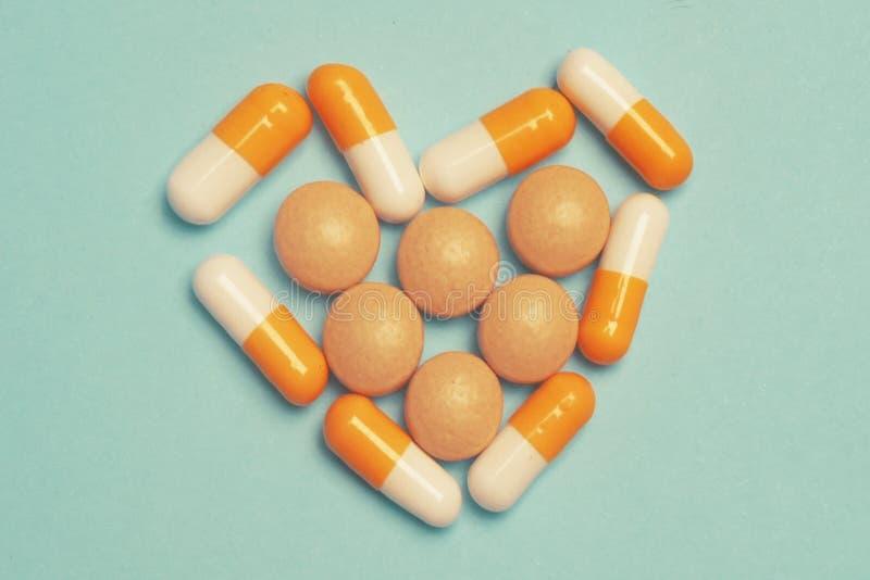 Pillen op een blauwe achtergrond Geassorteerde farmaceutische geneeskundepillen, tabletten en capsules, gezondheidsmacro Hartpill royalty-vrije stock afbeelding
