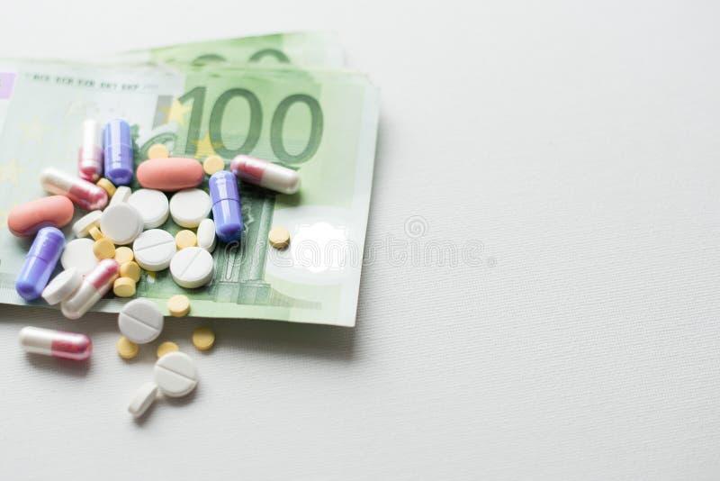 Pillen op euro geld dat op witte achtergrond wordt geïsoleerd Geneeskundeuitgaven Plaats voor tekst royalty-vrije stock afbeelding