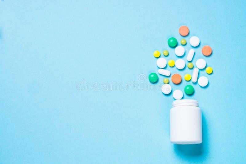 Pillen, tabletten en vitamine op blauw stock afbeelding
