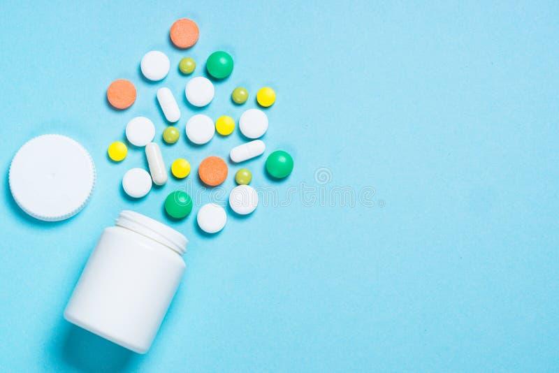 Pillen, tabletten en vitamine op blauw stock foto