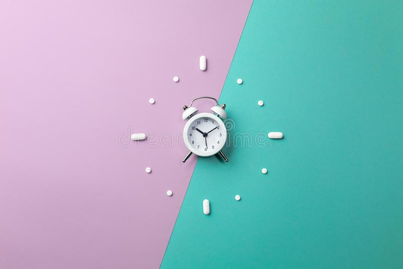 Pillen, Tabletten und weißer Wecker auf buntem Hintergrund Medizinisches und Gesundheitskonzept in der minimalen Art lizenzfreie stockfotos