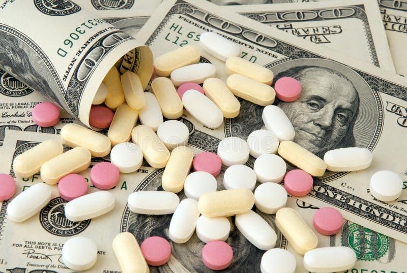 Pillen und Geld lizenzfreie stockfotografie