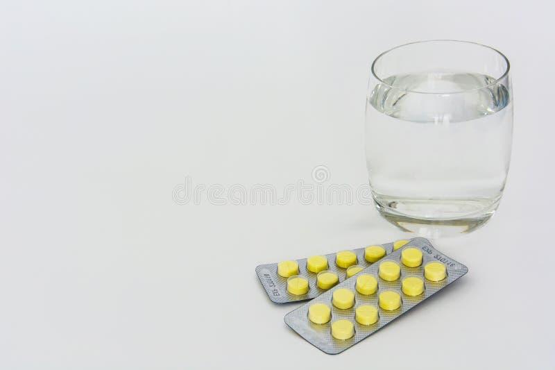 Pillen van geneeskunde met glas drinkwater op witte achtergrond wordt geïsoleerd die royalty-vrije stock fotografie