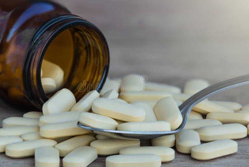 Pillen of vitamine in Geneeskundeflessen op de lepelachtergrond stock afbeeldingen
