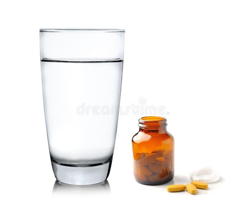 Pillen von der Flasche und vom Glas Wasser auf weißem backgroun stockbilder