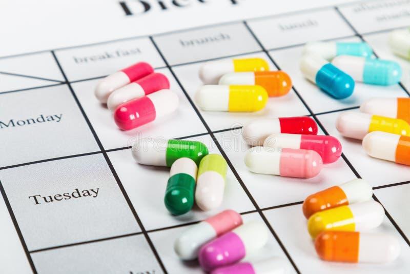 Pillen von verschiedenen Farben auf einem Kalender stockfoto