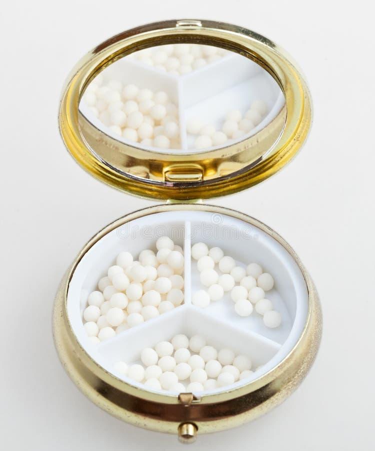 Pillendoos met de ballen van de suikerhomeopathie royalty-vrije stock afbeelding