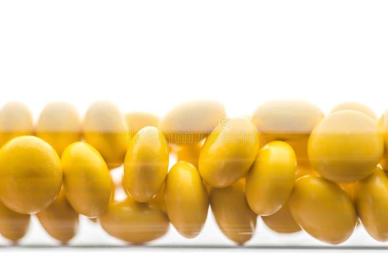 Piller eller minnestavlor f?r medicin tappar gula i den bruna glasflaskan p? vit bakgrund Isolat p? en vit bakgrund royaltyfria foton