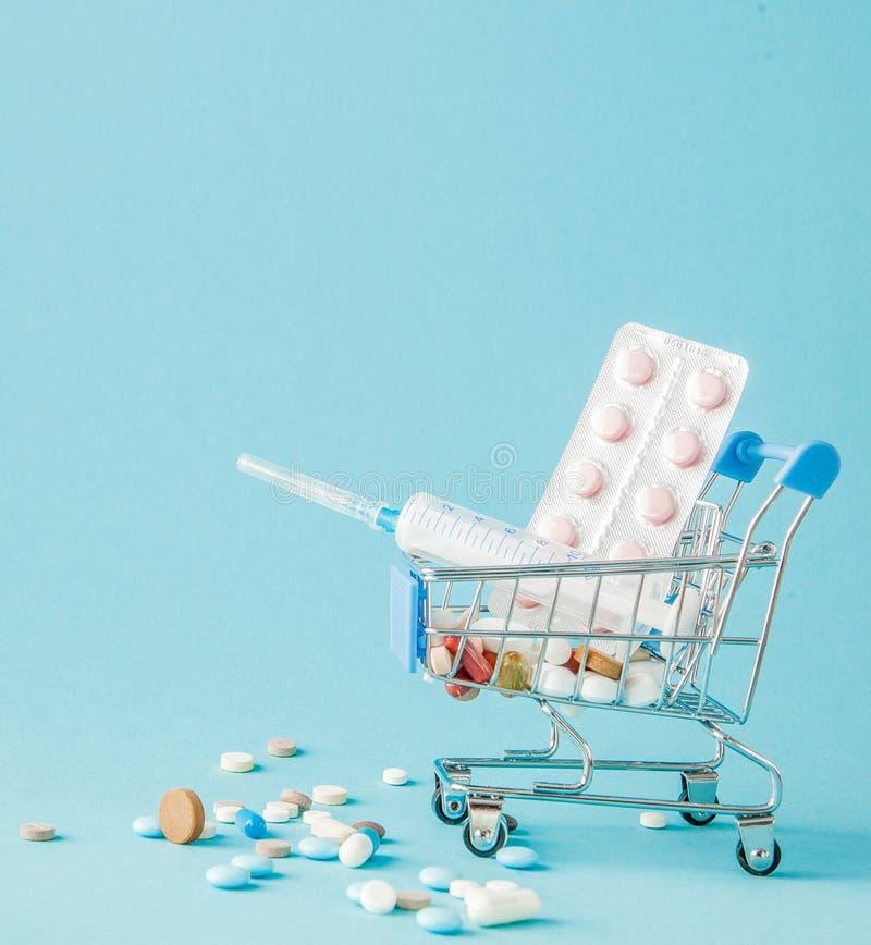 Piller och medicinsk injektion, i att shoppa spårvagnen på blå bakgrund Idérik idé för hälsovårdkostnad, apotek, hälsa royaltyfri bild