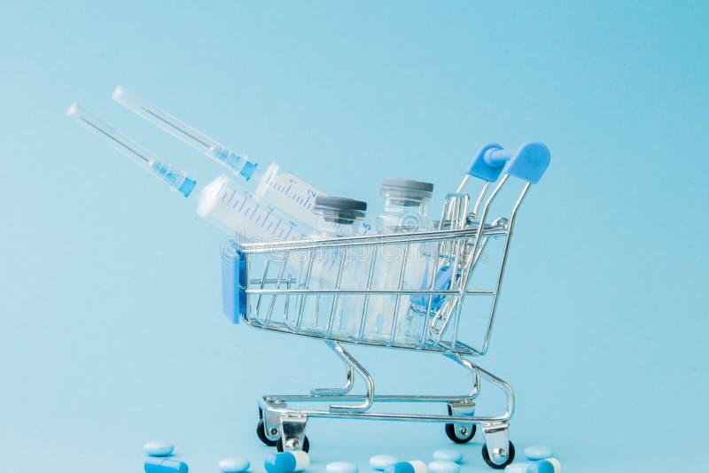 Piller och medicinsk injektion, i att shoppa sp?rvagnen p? bl? bakgrund Idérik idé för hälsovårdkostnad, apotek arkivfoton