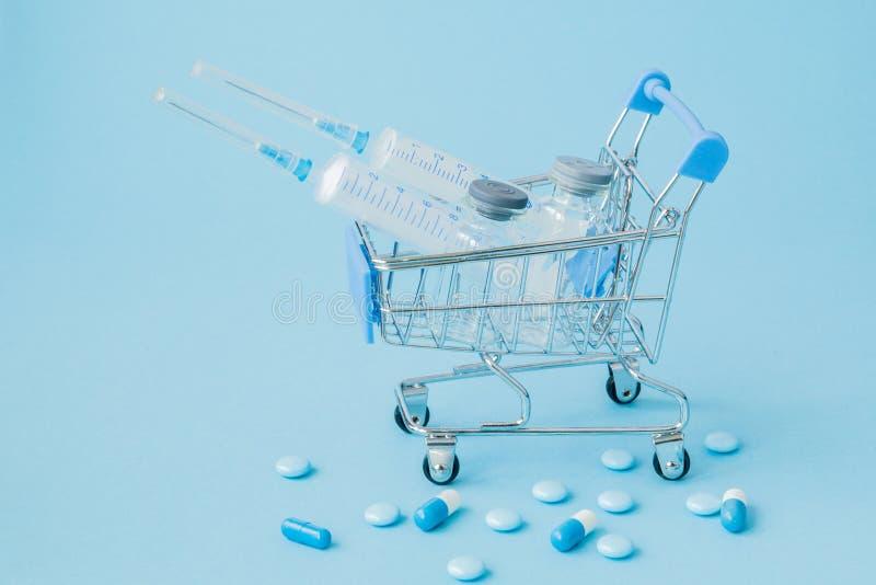 Piller och medicinsk injektion, i att shoppa sp?rvagnen p? bl? bakgrund Id?rik id? f?r h?lsov?rdkostnad, apotek, h?lsa royaltyfria bilder