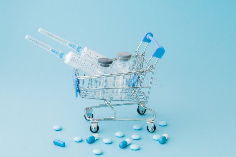 Piller och medicinsk injektion, i att shoppa sp?rvagnen p? bl? bakgrund Id?rik id? f?r h?lsov?rdkostnad, apotek, h?lsa royaltyfri fotografi