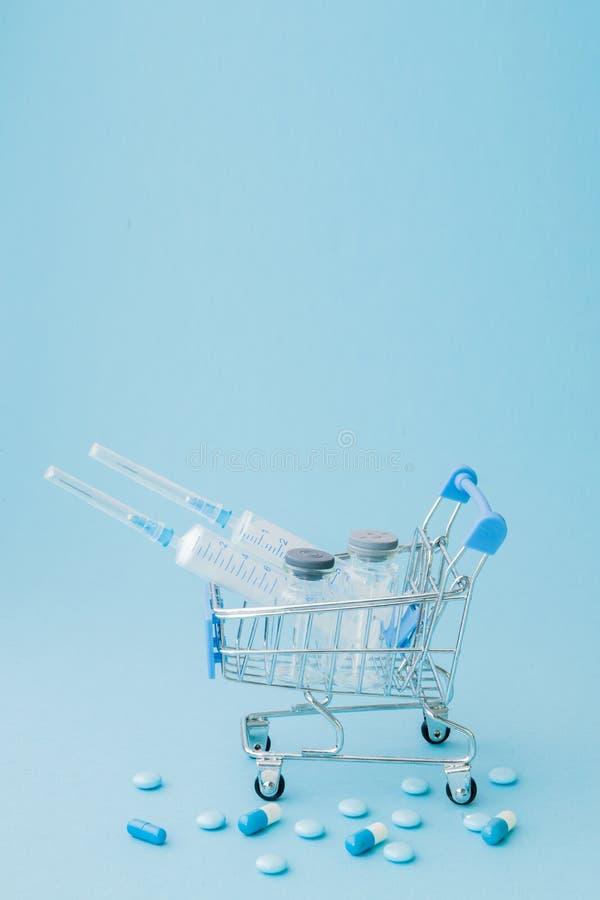 Piller och medicinsk injektion, i att shoppa sp?rvagnen p? bl? bakgrund Id?rik id? f?r h?lsov?rdkostnad, apotek, h?lsa arkivbilder