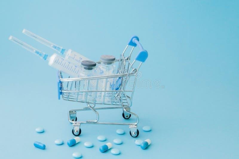 Piller och medicinsk injektion, i att shoppa sp?rvagnen p? bl? bakgrund Id?rik id? f?r h?lsov?rdkostnad, apotek, h?lsa royaltyfri foto