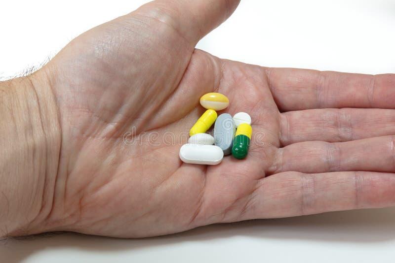 Piller och minnestavlaläkarbehandlingen i gömma i handflatan av a mans handen arkivbild