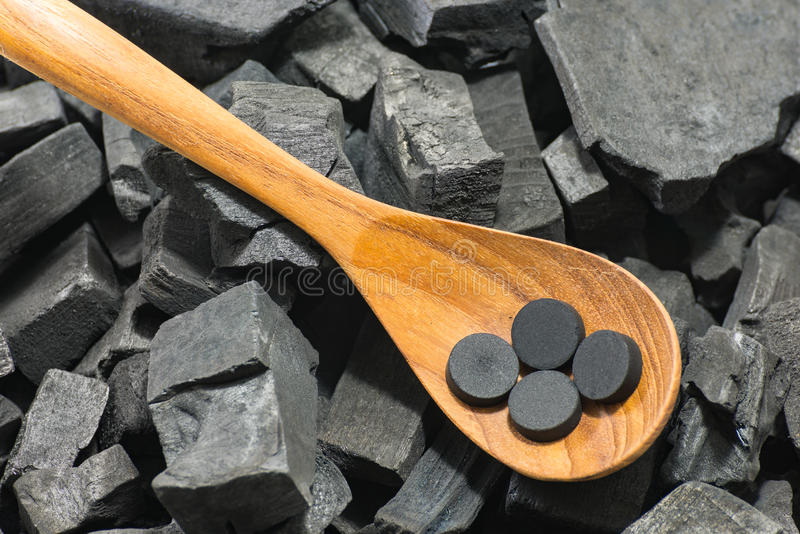 Pillola attivata del carbonio in cucchiaio di legno su struttura del carbone fotografia stock libera da diritti