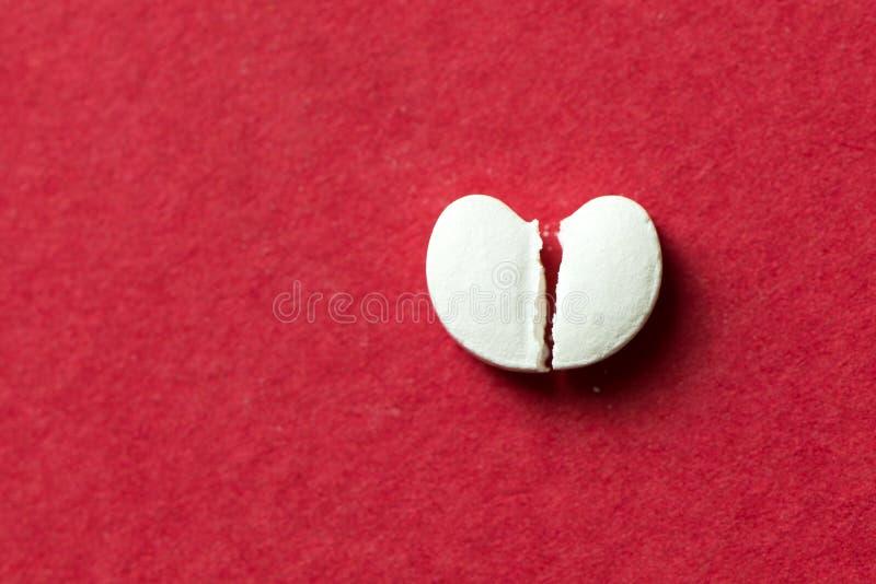 Pillola a forma di del cuore incrinata a metà fotografia stock