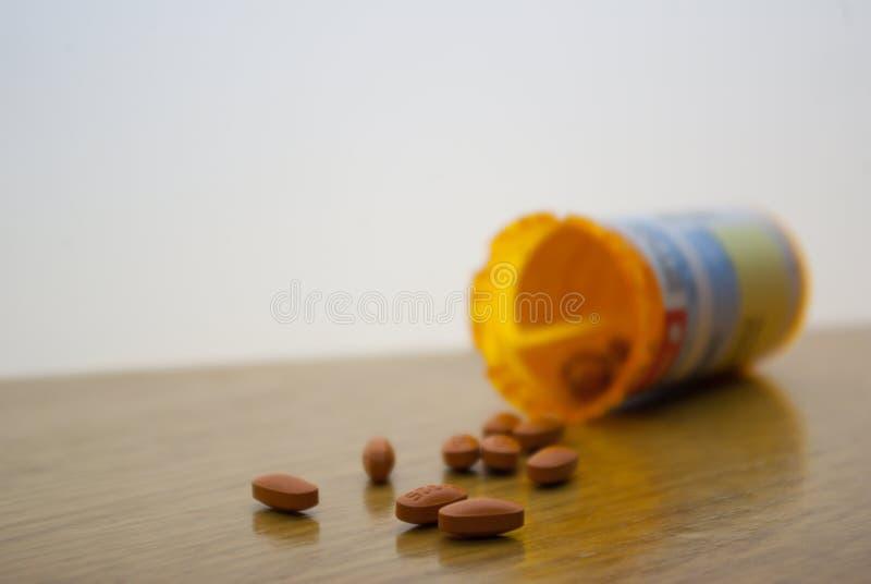 Pillole arancio rovesciate su superficie bianca fotografia stock