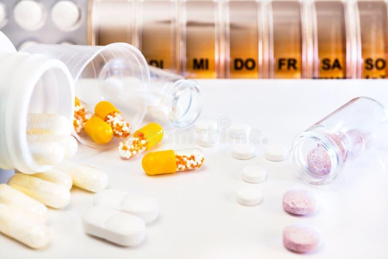 Pillole assortite, capsule e un contenitore della pillola fotografia stock