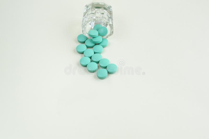 Pillole che si rovesciano dalla bottiglia di pillola su fondo bianco Copi lo spazio fotografia stock