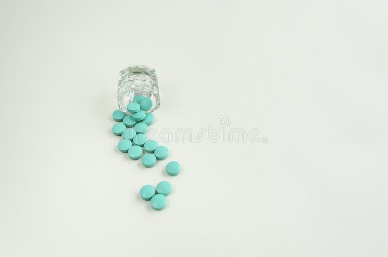 Pillole che si rovesciano dalla tazza della pillola su fondo bianco Copi lo spazio fotografia stock libera da diritti