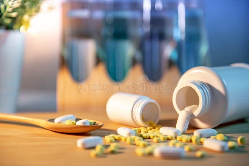 Pillole che si rovesciano dalle bottiglie di pillola sulla tavola di legno fotografie stock libere da diritti