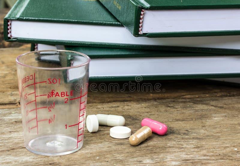 Pillole che si rovesciano sulla vecchia tavola di legno immagini stock libere da diritti
