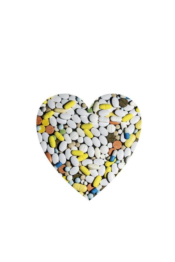 Pillole colorate per il trattamento le malattie e della dipendenza sotto forma di cuore fotografie stock