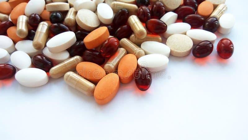 Pillole, compresse e capsule farmaceutiche variopinte ordinate della medicina su fondo bianco immagini stock