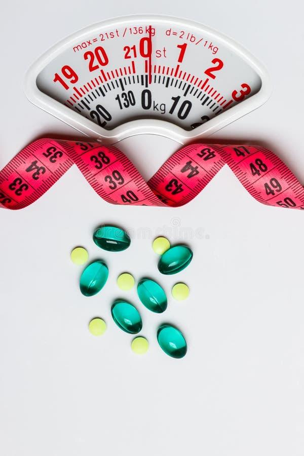 Pillole con nastro adesivo di misurazione sulle scale bianche fotografia stock